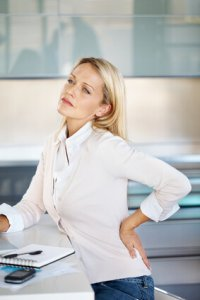 Portrait of successful mature business woman with pain in lower back
